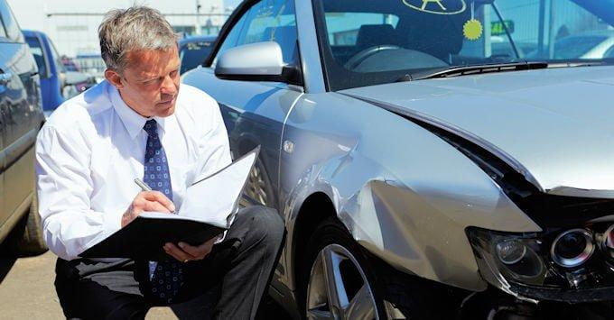 Insurance adjuster looking at a damaged car