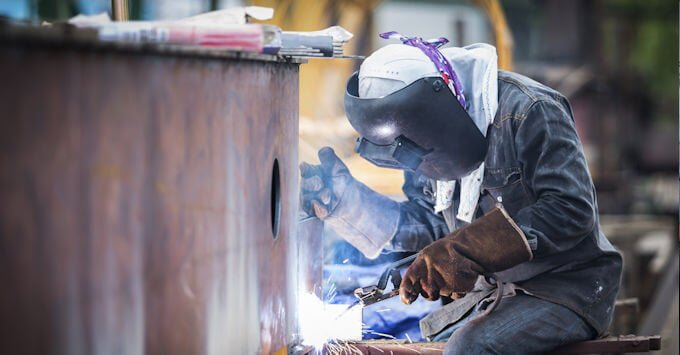 Employee Welding at Manufacturing Plant